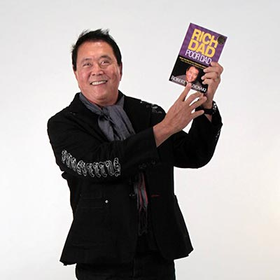 Robert Kiyosaki holding his New York Times best-selling book, Rich Dad Poor Dad