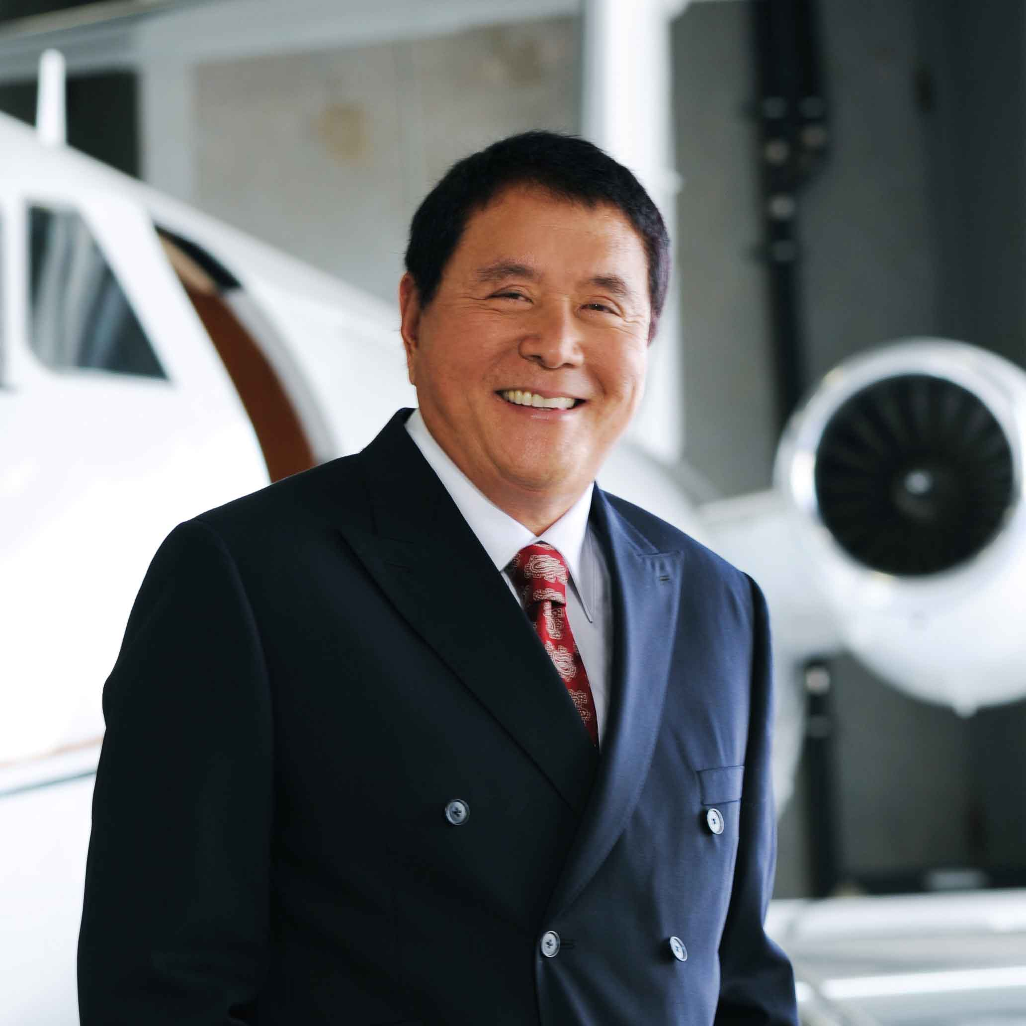 Robert Kiyosaki standing by a private jet in an airplane hanger.