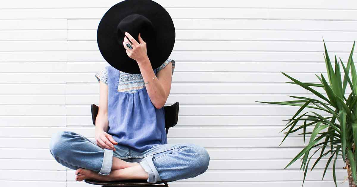 woman hiding her face with a large hat while sitting cross-legged in a chair