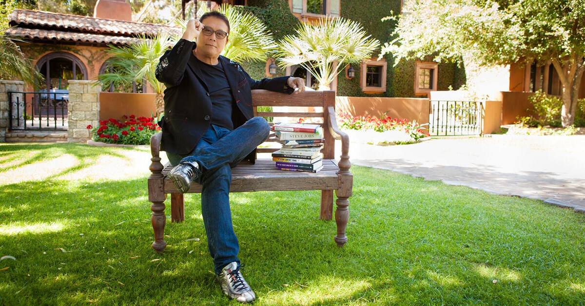 Robert Kiyosaki sitting on a bench in the courtyard of his house