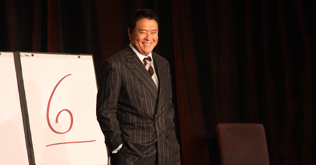 Robert Kiyosaki on stage in front of a flip board with the number 6 on it