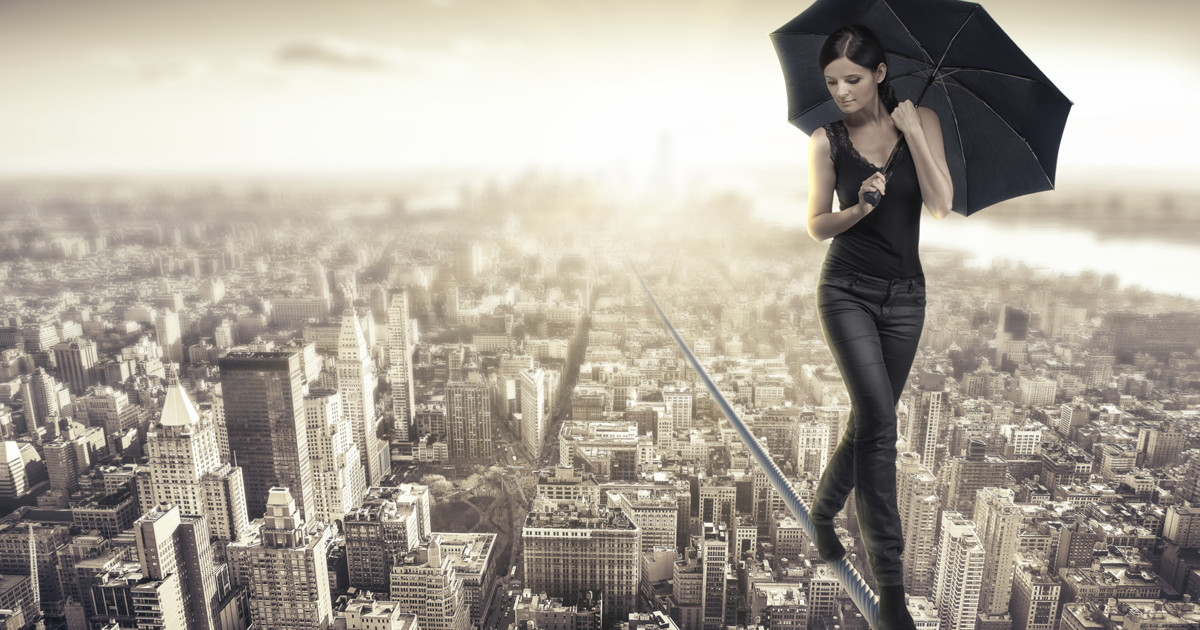 business woman walking a tightrope over a city