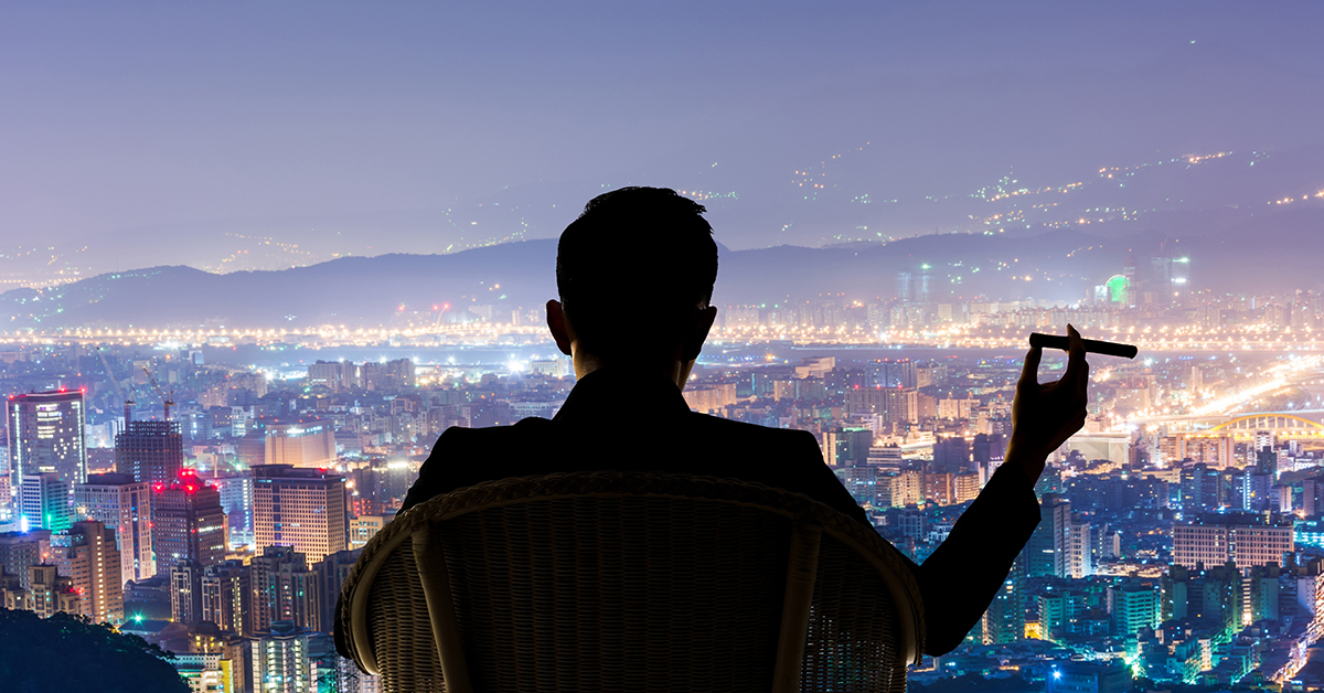 Silhouette of man sitting in chair with cigar looking out into the city lights