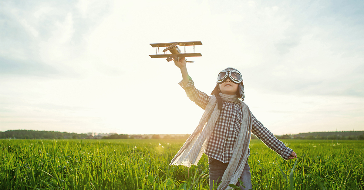 Young boy in flight mask & scarf runs in field of tall grass holds wooden airplane above head
