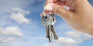hand holding keys against cloudy background