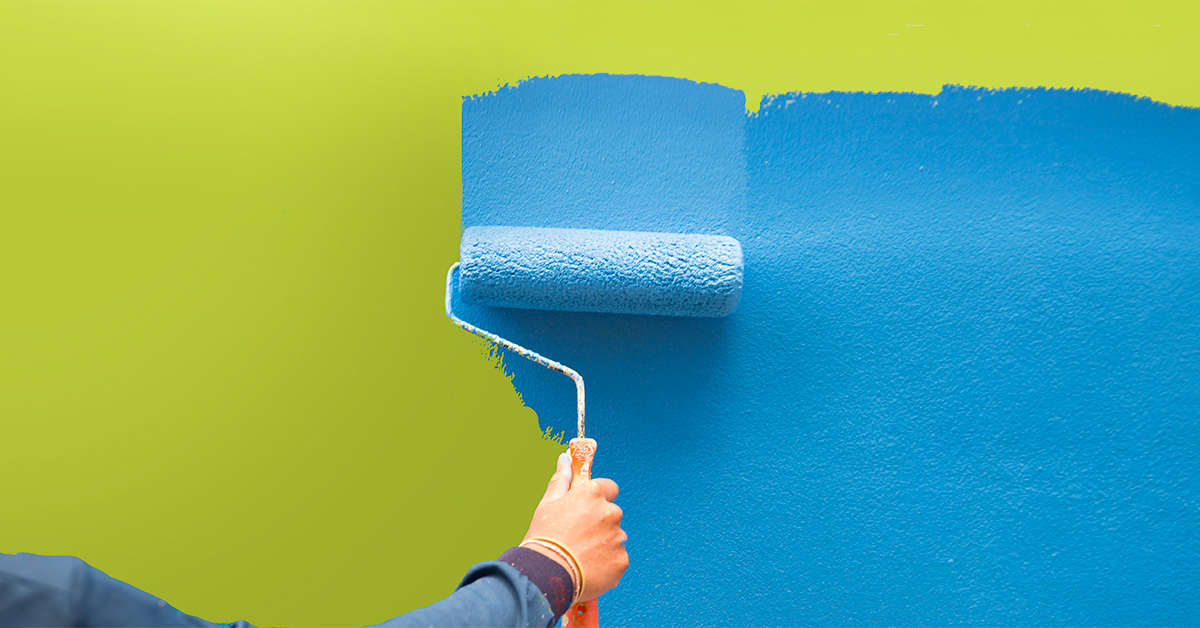 Man painting blue paint onto green wall with a roller