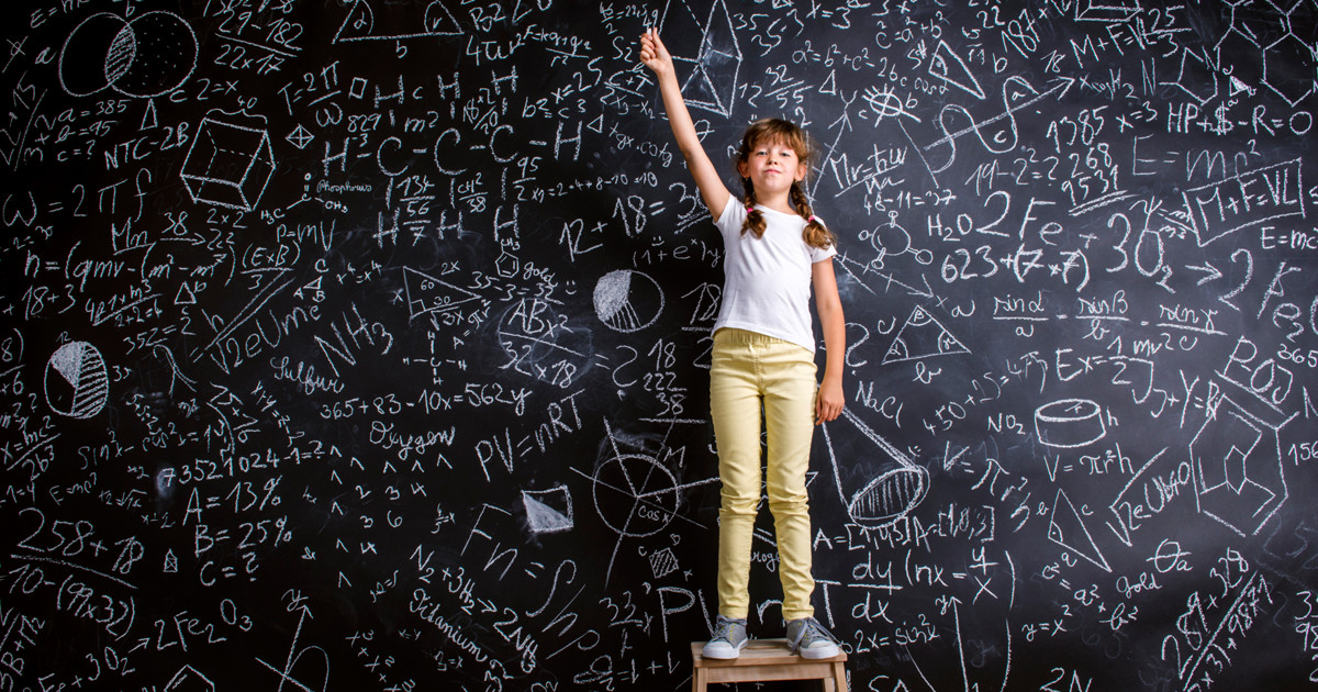 young girl student standing triumphant on a stool in a classroom