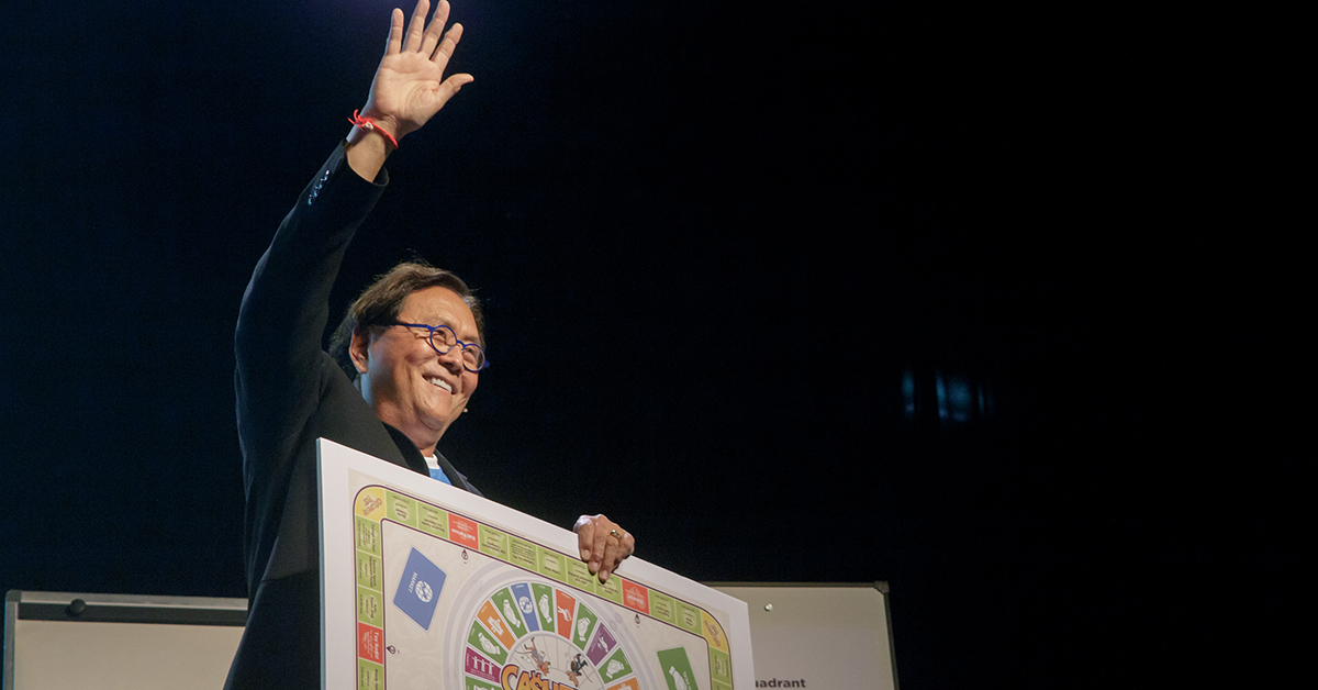 Robert Kiyosaki on staging waving to the crowd showing the CASHFLOW(r) board game