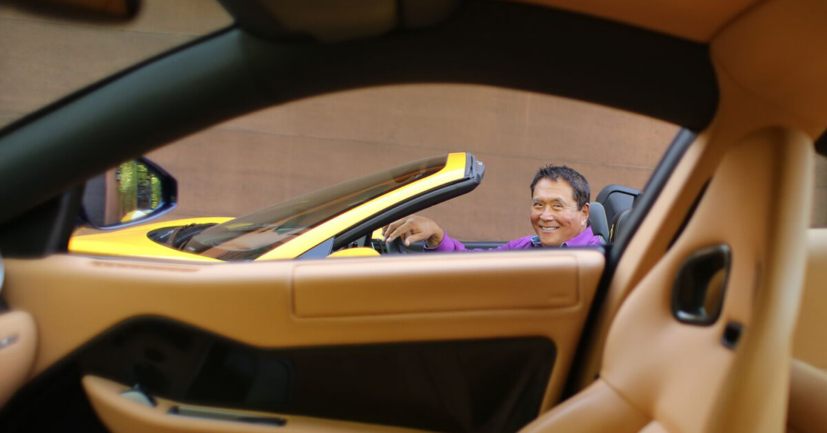 Robert Kiyosaki in his yellow Ferrari
